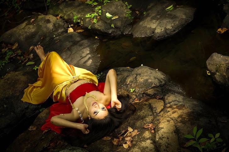 岩場にあおむけに寝るタイ人女性
