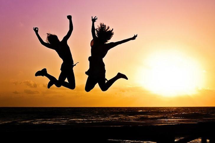 夕暮れを背景に飛び跳ねる若者たち