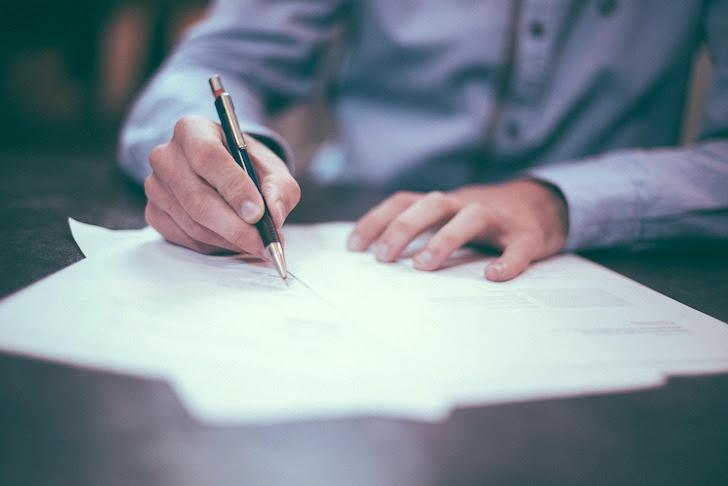 契約書にサインをするスーツ姿の男性