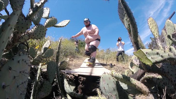 スケートボードでサボテンの山を越えようとする男性