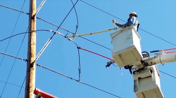 高圧電線を切断しようとしている男性