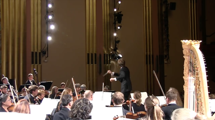 悲鳴を上げた聴衆を振り返って一目する指揮者