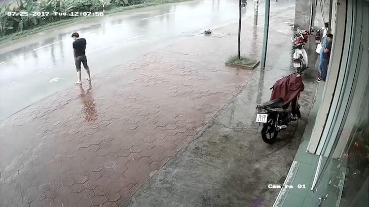 道路の水たまりに立ち小便をする男性