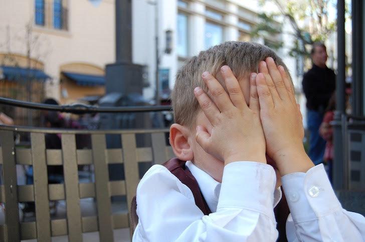 顔を両手で隠して恥ずかしがる少年