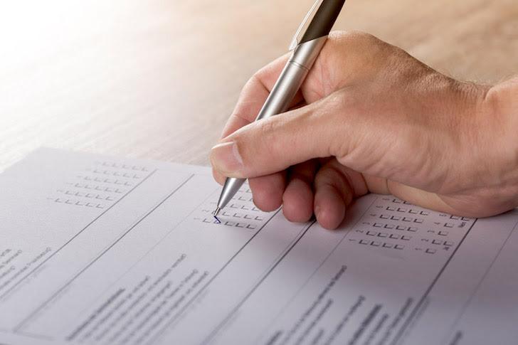 アンケート用紙にペンでき記入する男性の手