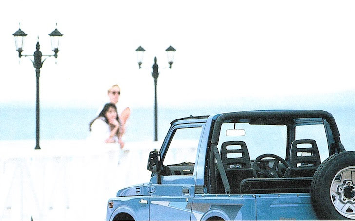 海岸線に止まる青色のスズキ・ジムニーJA11