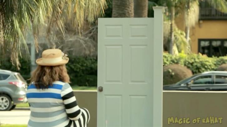 魔法のドアを不思議そうに見つめる女性