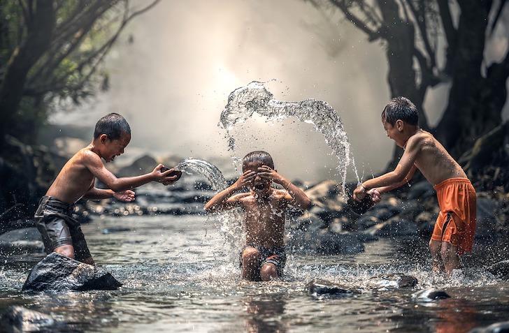 水を掛け合うタイの少年たち