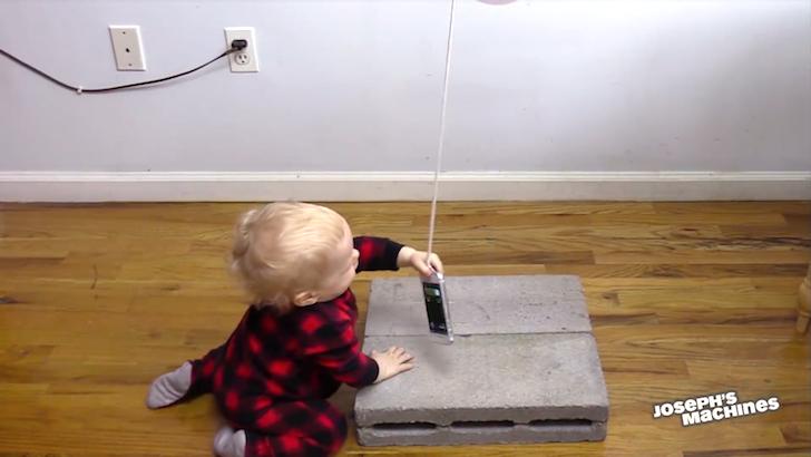 ひもにつるされたスマートフォンを引っ張る赤ちゃん