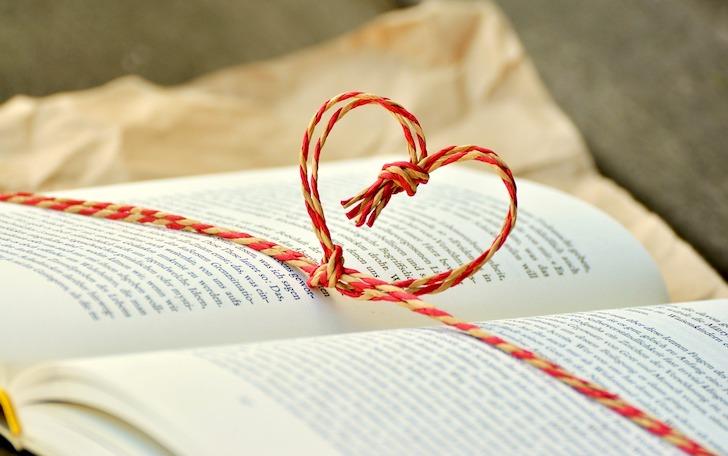 開いた本の上に置かれたひもで方取ったハートマーク