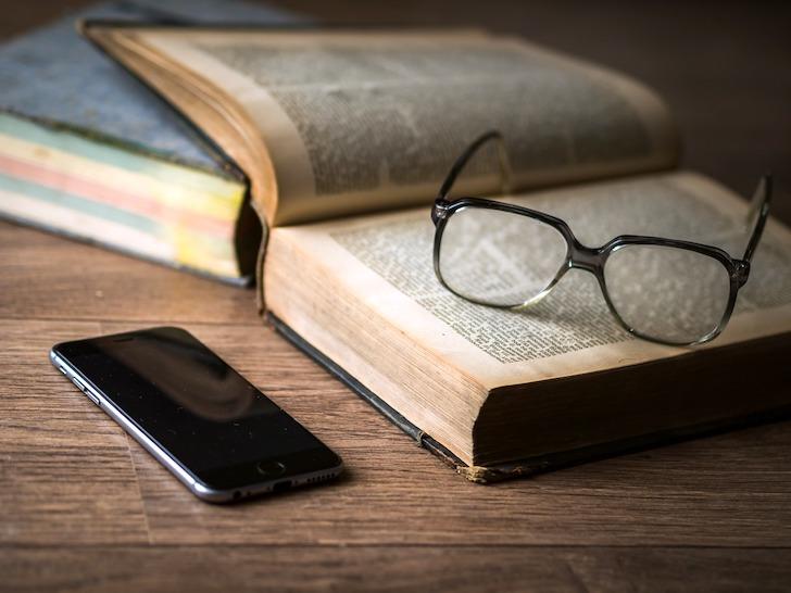 開けられた本の上に置かれた眼鏡と横にあるスマートフォン