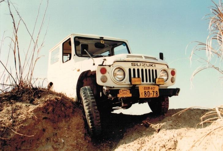 悪路にタイヤを取られる白色のスズキ・ジムニーSJ10型