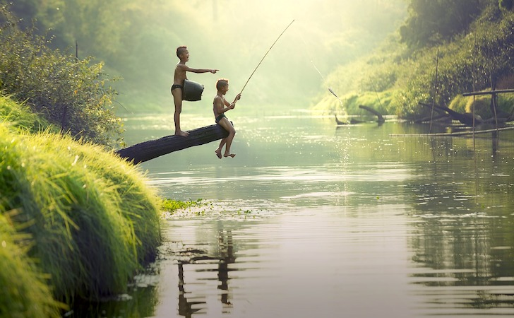 河原で釣りをするタイの少年たち