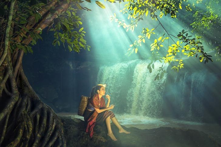 木漏れ日に照らされる川のほとりにたたずむ女性