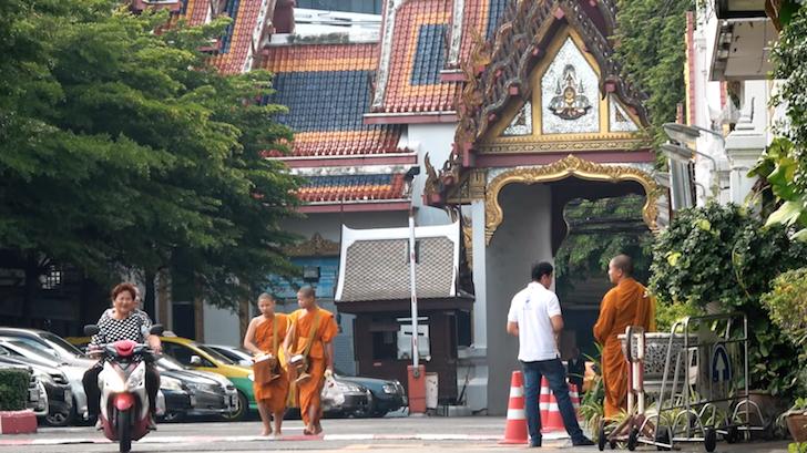 バンコクにある駐車場を歩く僧侶とバイクで通り過ぎる女性たち