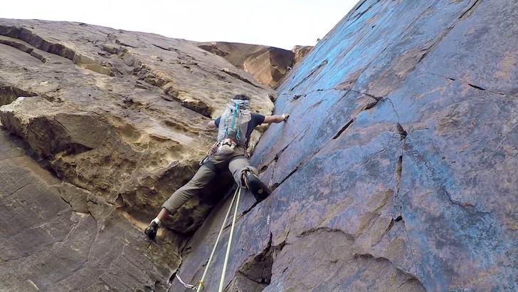 断崖絶壁を器具を用いずよじ登る男性
