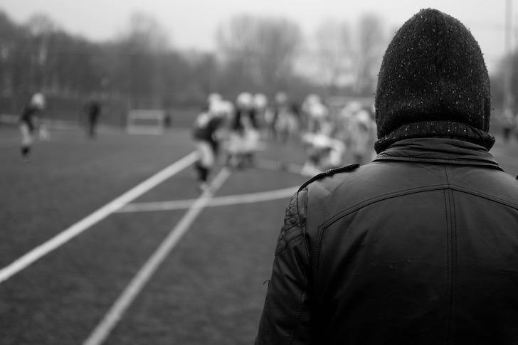 アメリカンフットボールの練習を眺める監督