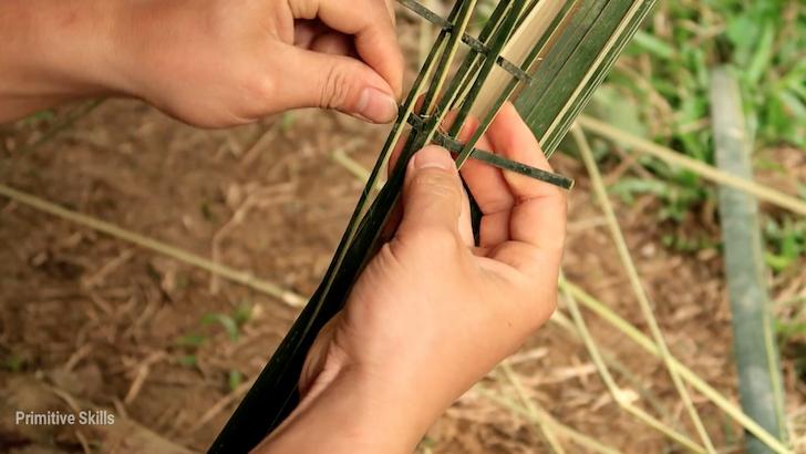 竹で鳥籠をこしらえる男性