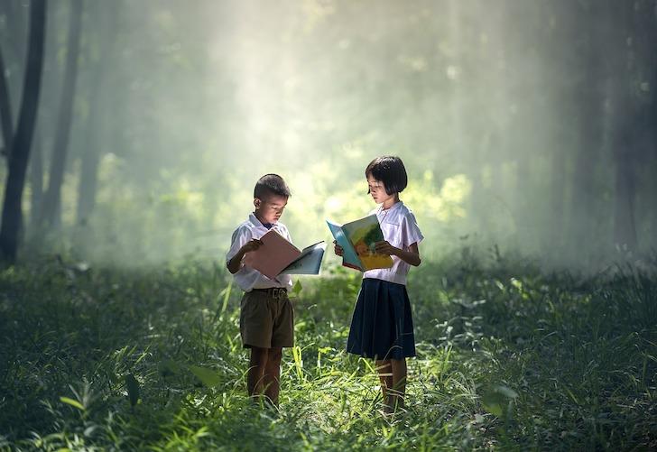 森の中で本を読むタイ人の子どもだち