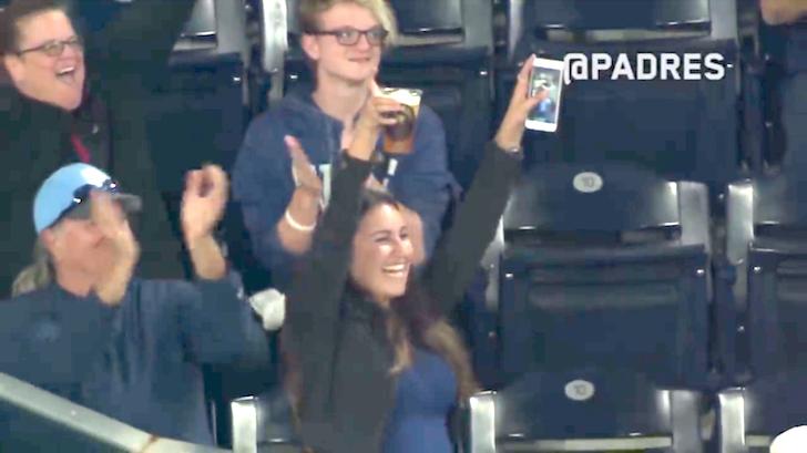 ビールの容器に入ったボールを観客たちに見せる女性