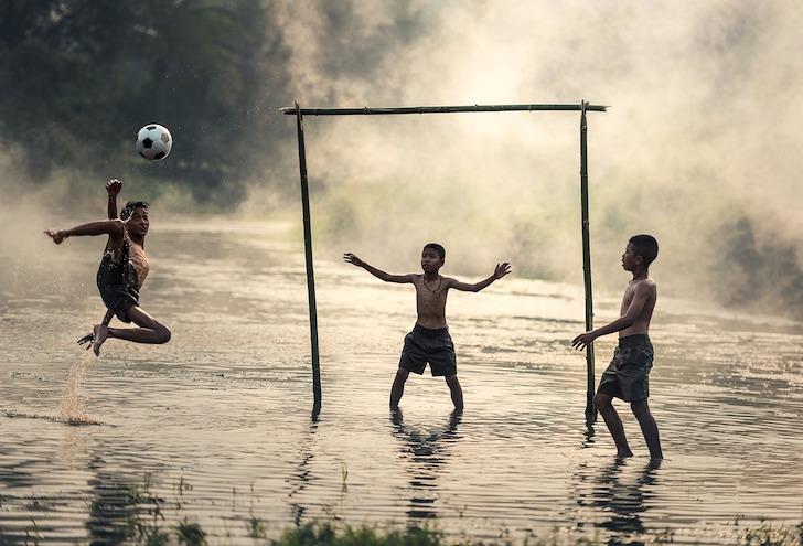 川辺でサッカーをして遊ぶタイ人の子どもたち