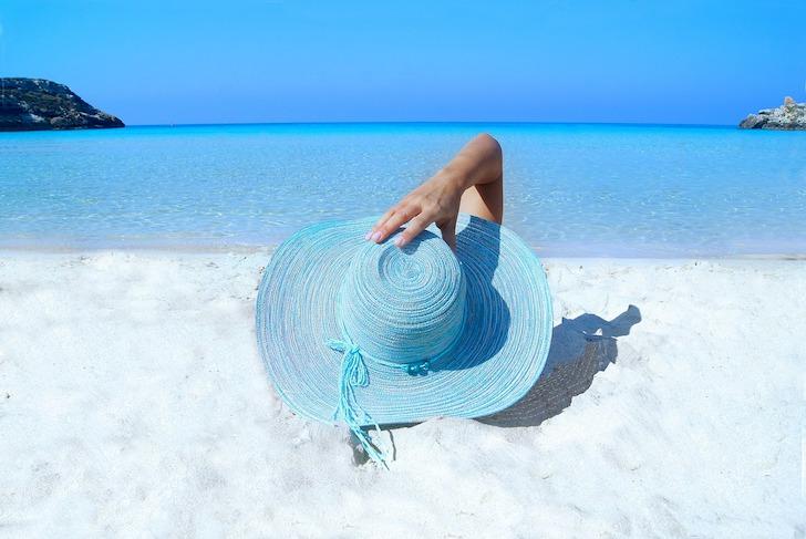 砂浜で水色の麦わら帽をかぶって横になる女性