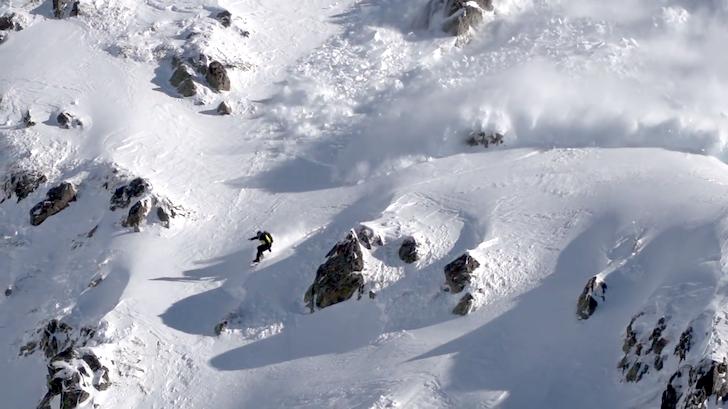 表層雪崩から必死で逃げようとするスノーボーダー