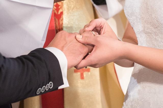 新婦が新郎に指輪をはめている手をクローズアップ