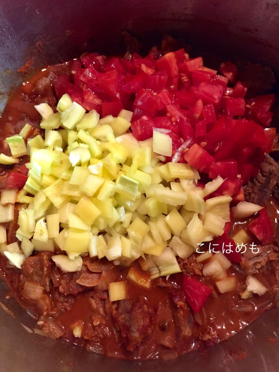 トマト(角切り)、パプリカ(角切り)を入れフタをして煮る。