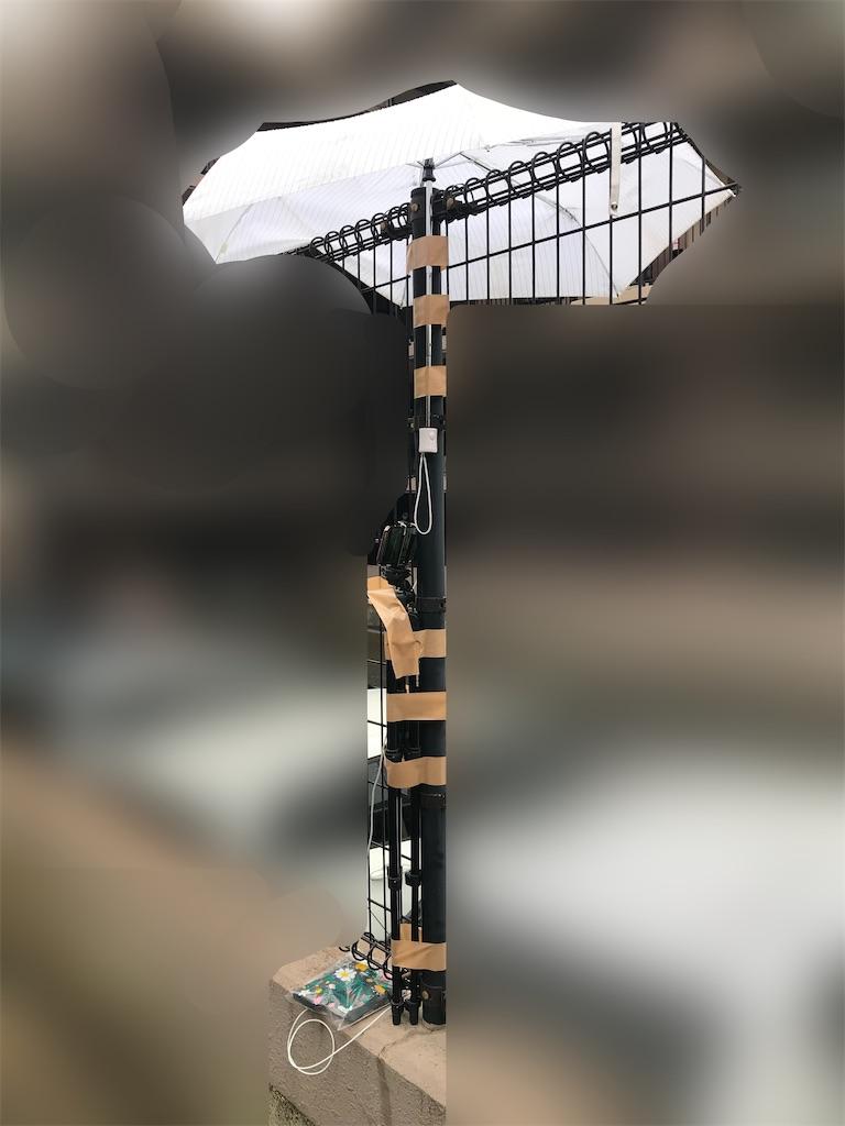 傘とiPhoneを柵に取り付けている写真