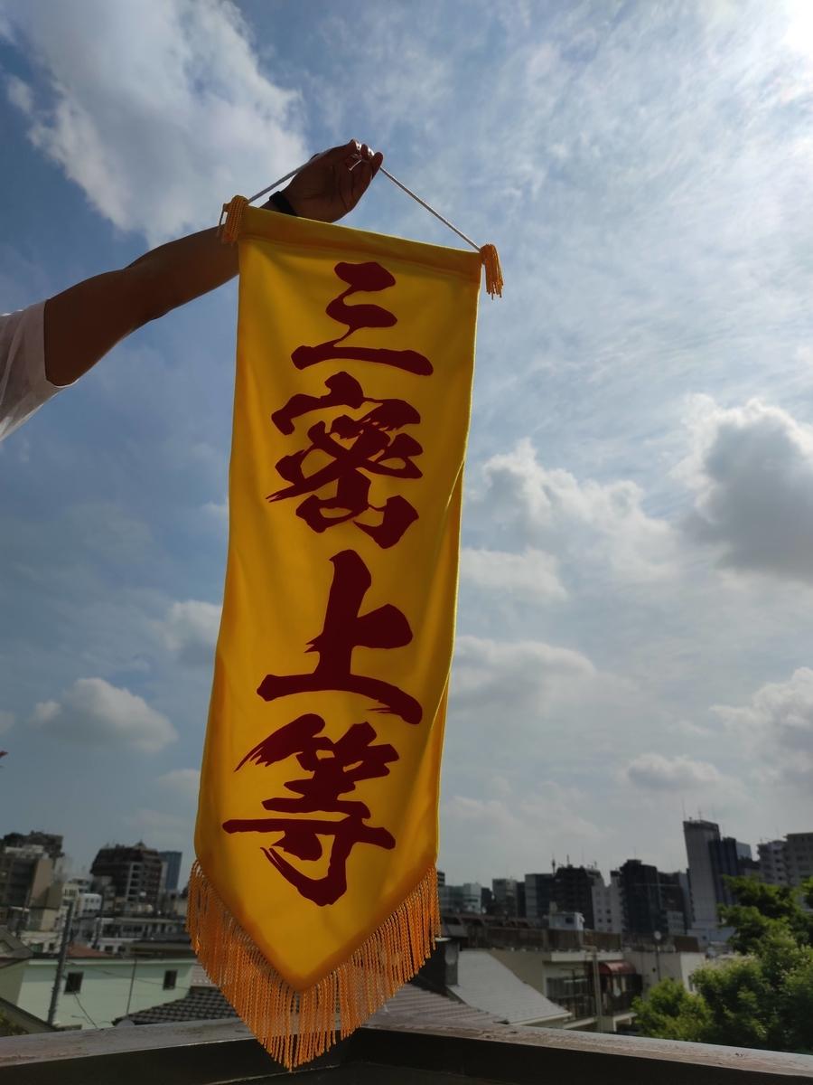 青空を背にした三密上等の旗