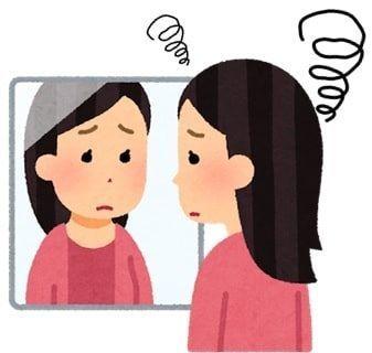 悲しそうに鏡を見ている女性