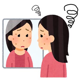 シミを気にして鏡を見つめている女性