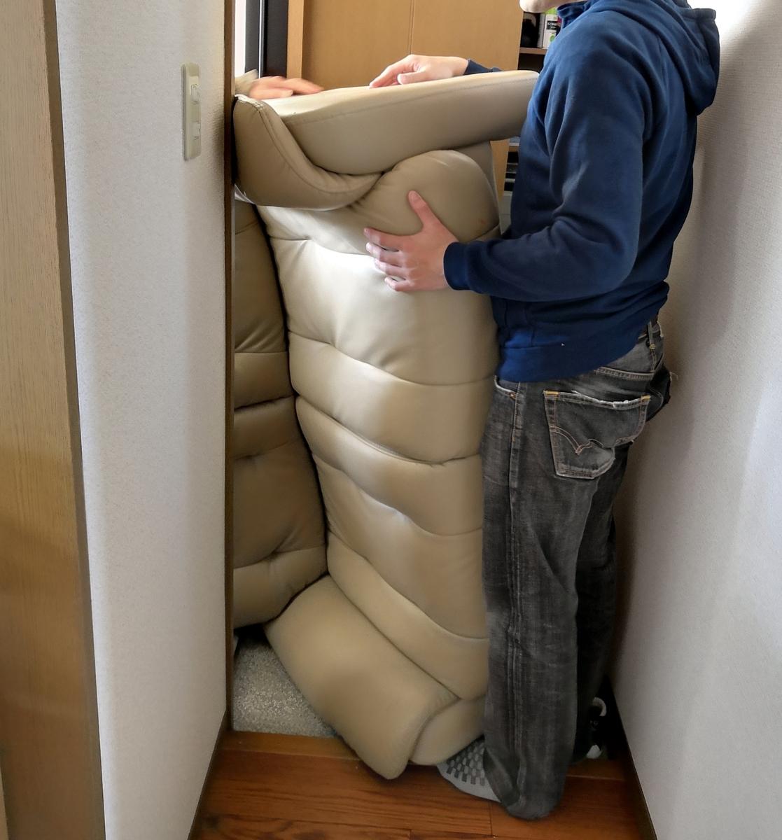 玄関から運び出されるソファ
