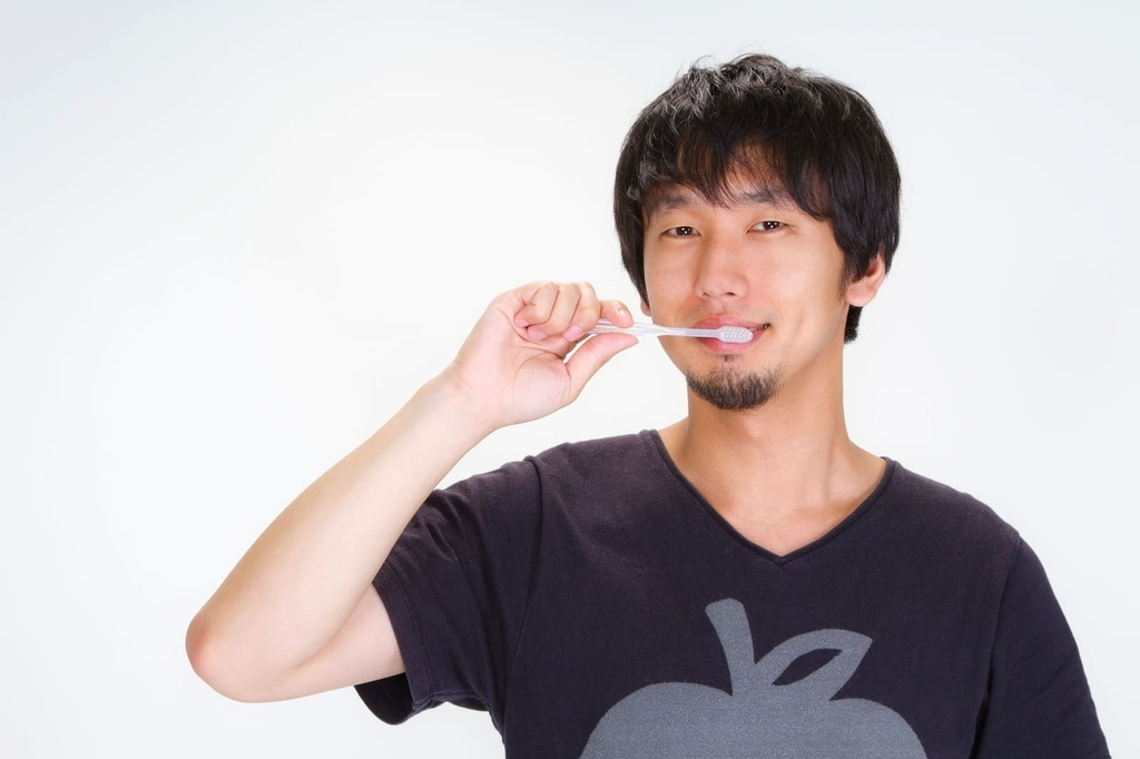 朝の歯磨きを笑顔でする男性