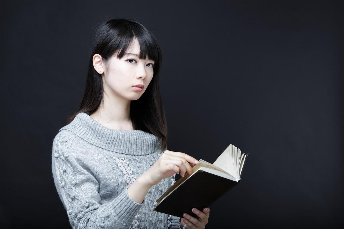 立ちながら本を読む女性