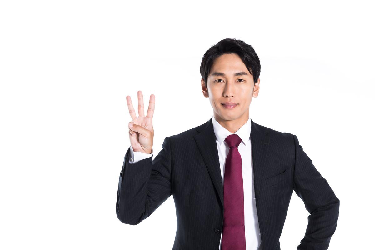 3本指を立てる男性