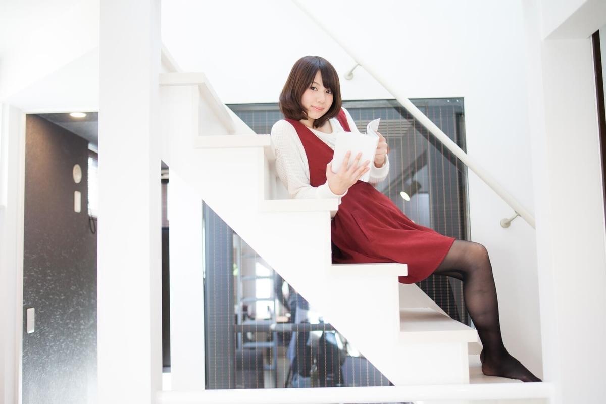 階段で本を読む女性
