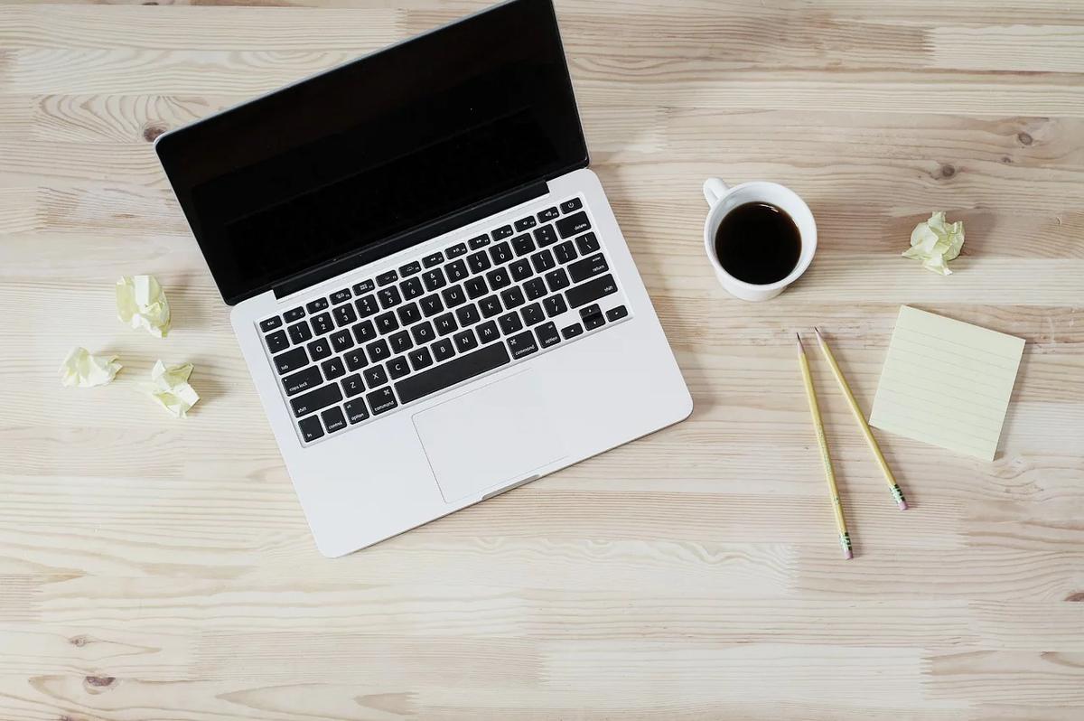 デスクに置かれているパソコンとコーヒー