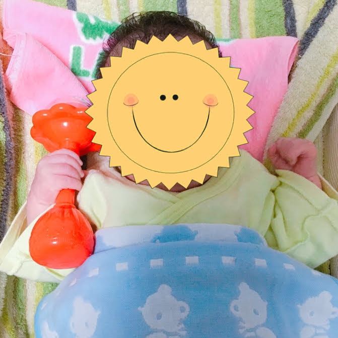 ラトルを握る赤ちゃん