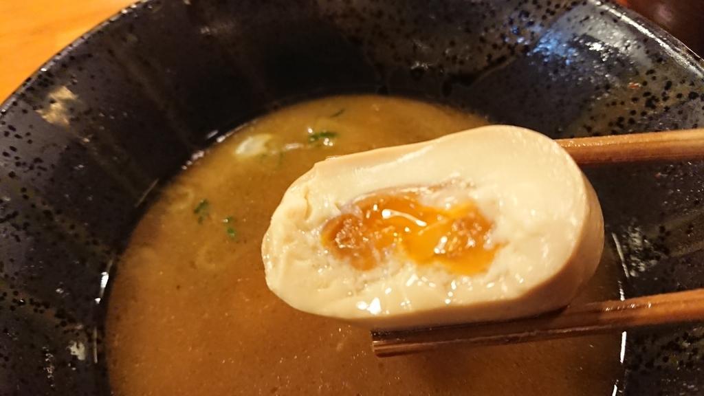 半分にきった味付卵を箸でつまんだところ