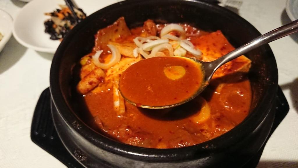 スプーンですくうキムチチゲ鍋のスープ