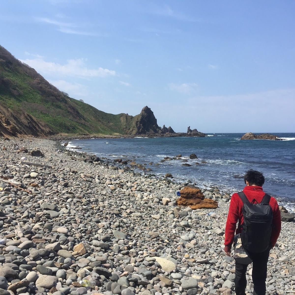 積丹の岩場に続く海岸を歩くkuro隊員