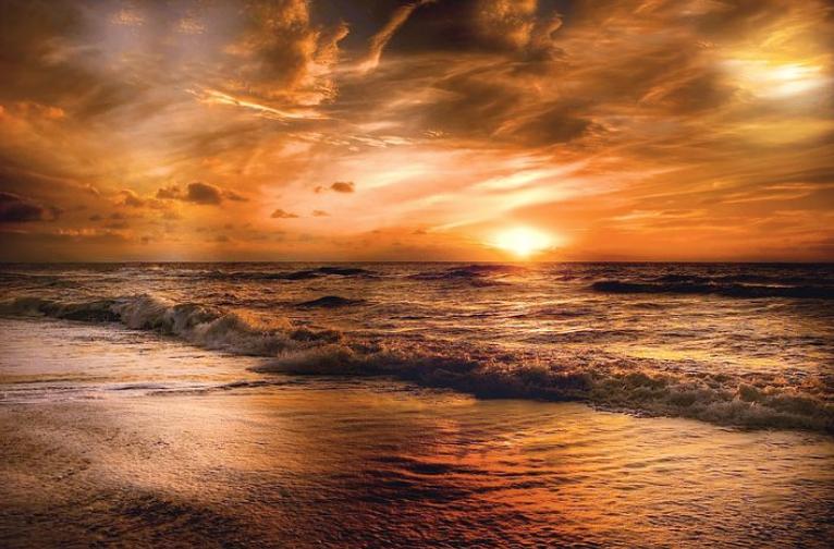 海辺の黄金色に輝く美し夜明け。空と海とのコントラストが非常に美しい