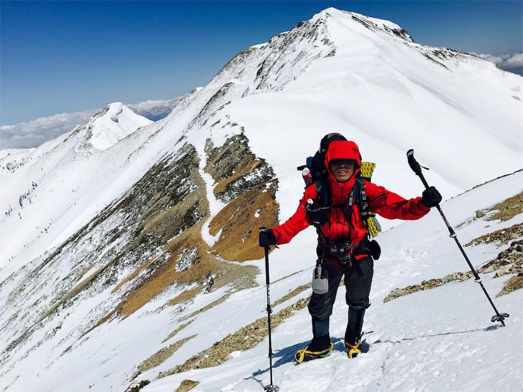 ハードシェルをきて冬山登山をする男性