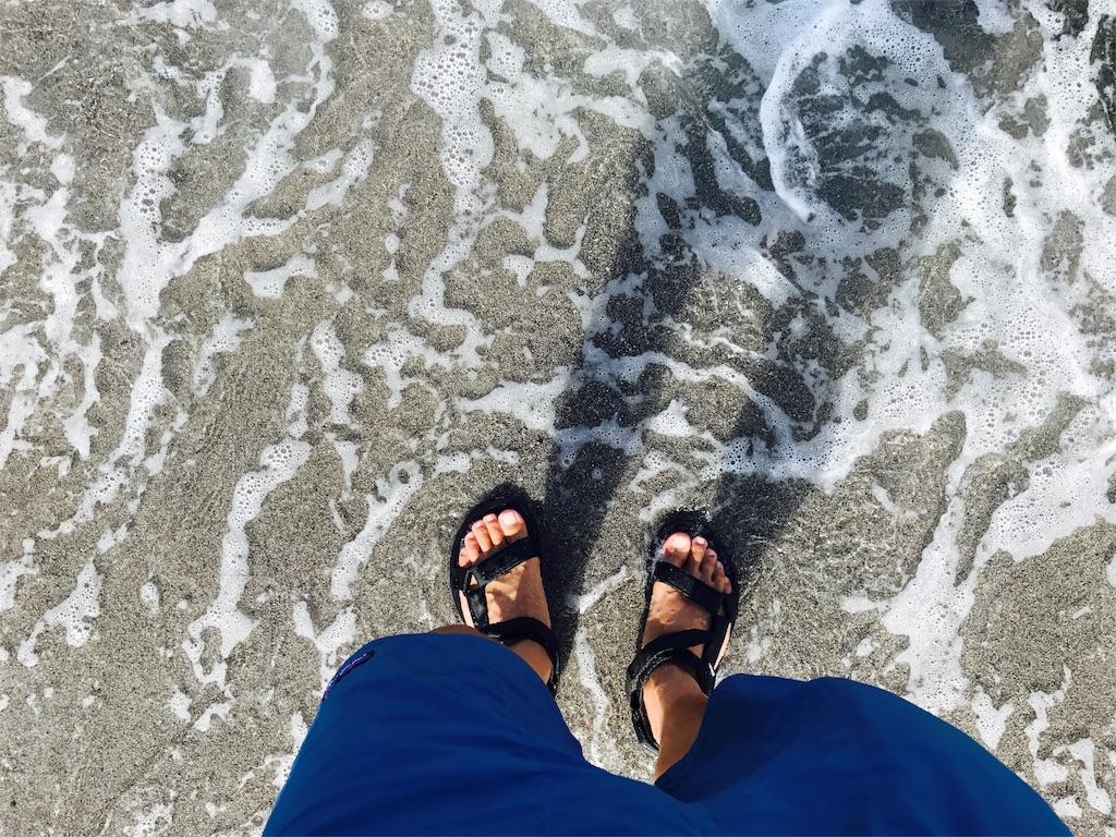 バギーズショーツを履いて海に入る男性