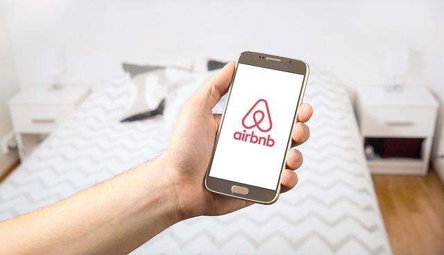 部屋でスマホを手にAirbnbアプリを起動している
