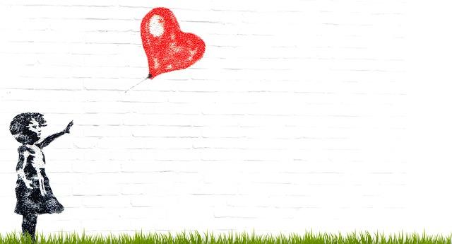 白いレンガ壁に描かれた1人の少女とハート型風船の壁画