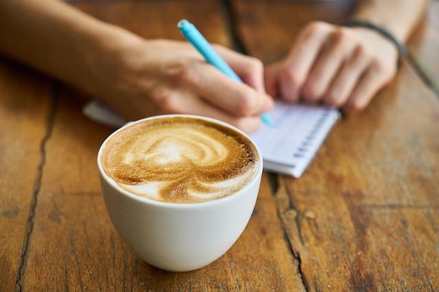 机の上のカフェオレとメモ帳