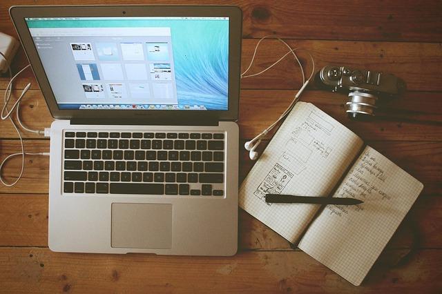 ノートパソコンとメモ帳と一眼レフカメラ